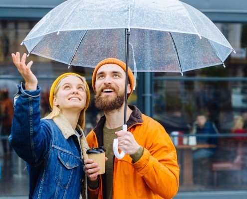 Hipster couple under umbrella in rainy spring cold weather